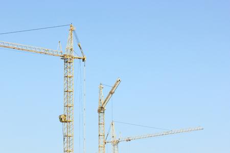 bilding: Construction cranes on blue sky background. Stock Photo
