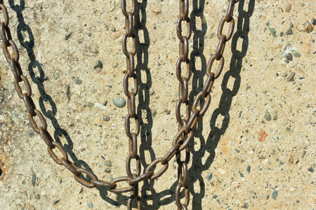 catena: Chain hanging on a concrete wall background.