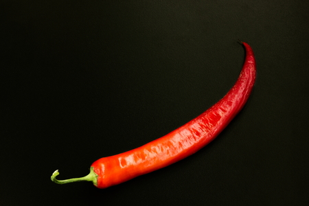 racy: The pod of red pepper on a black background. Stock Photo