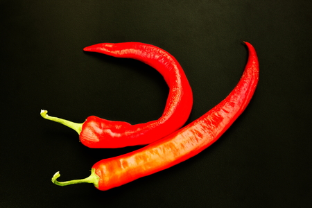 vermeil: Two pods of red pepper on a black background.