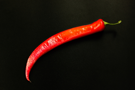 red pepper: The pod of red pepper on a black background. Stock Photo