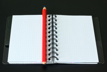 entries: Notebook and red pencil on a black background.