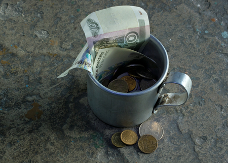 indigent: The aluminum mug with money.