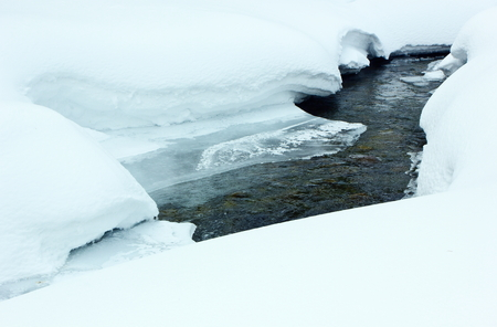 Rocky stream flowing among the snowdrifts.Tinted image.