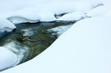 inhospitable: Rocky stream flowing among the snowdrifts.Tinted image.