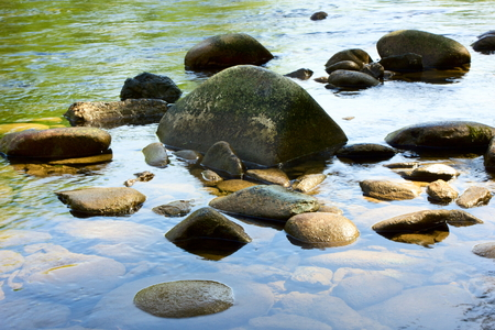 pebles: Stones lying in the water on the river bank.