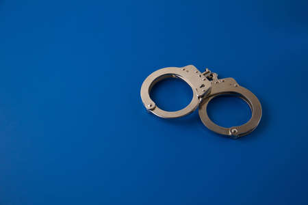 Closed handcuffs on blue background Stock Photo - 12086580