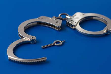 detained: Las esposas abiertas con llave en color azul Foto de archivo