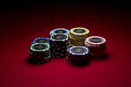 Poker chips on red surface Reklamní fotografie