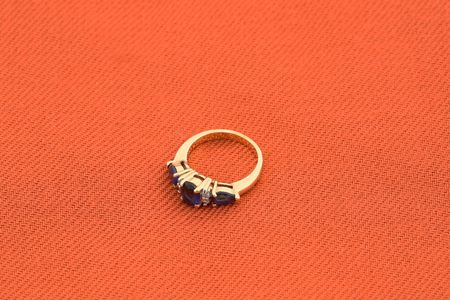 jewelery 022 gold ring with blue stone red background.