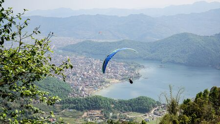Paragliders flying against the Himalayas , Pokhara , Nepal.
