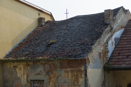 gutted: Abandoned and boarded up old house with missing roof tiles in Keszthely, Hungary.
