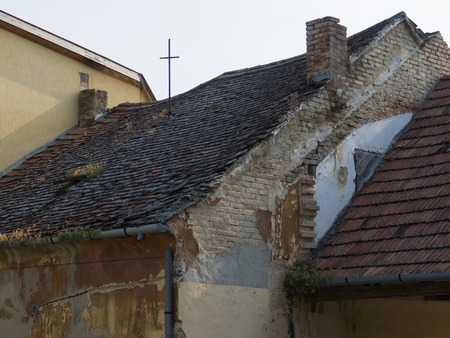 window graffiti: Abandoned and boarded up old house with missing roof tiles in Keszthely, Hungary.