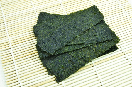 Roasted seaweed snack on bamboo mat background