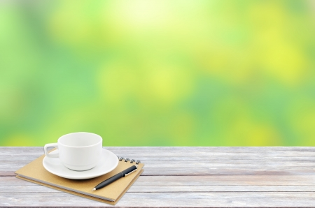coffee cup on wooden table with green bokeh background