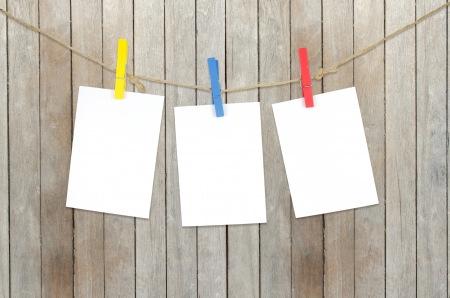 Three empty white photo frames hanging with clothespins on wooden background