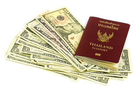 Thailand passport and roll of dollars money on white background photo
