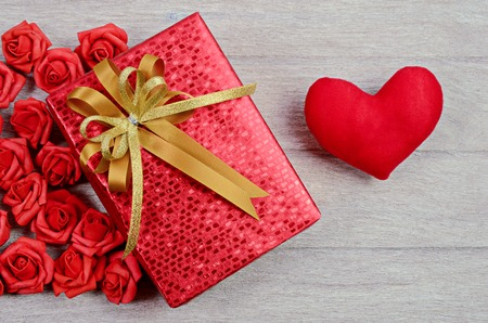 christmastide: red gift box on wood background