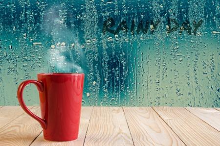 cup: taza de café roja con humo en el agua cae ventana de vidrio de fondo