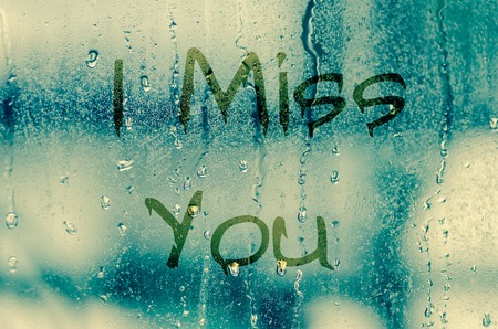 miss you: natural water drops on glass window with the text I miss you Stock Photo