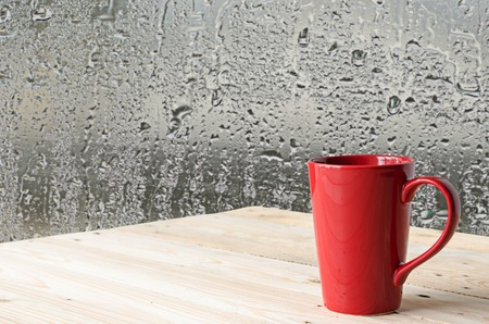 brewed: red coffee cup with natural water drops on glass window background Stock Photo