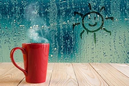 煙と太陽赤コーヒー カップに水滴ガラス ウィンドウの背景に署名します。 写真素材