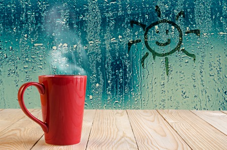 red coffee cup with smoke and sun sign on water drops glass window background Stockfoto