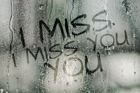 i miss you: natural water drops on glass window with the text I miss you Stock Photo