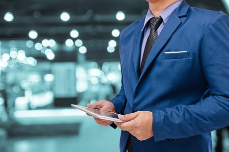 ejecutivo en oficina: Hombre de negocios que sostiene la tablilla en la mano en el fondo borroso Foto de archivo