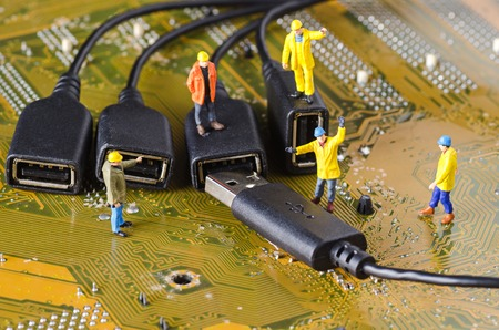 connection: Miniature Technicians try to connecting data cable Stock Photo