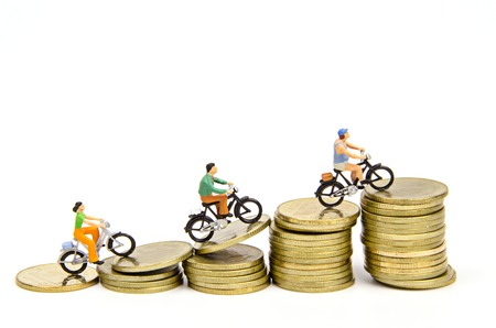 miniature people: Miniature people ride on stack of coins