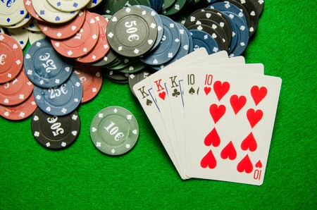 full house: Playing cards Full House and chips on green background Stock Photo