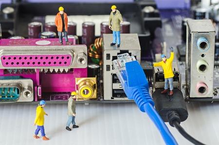 ingeniero: Equipo de ingenieros miniatura tratar de conectar los cables de Ethernet al puerto