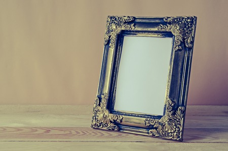 blank photo frame on wooden table