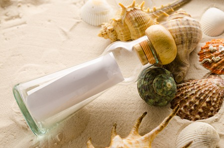 rescue west: bottle letter and sea shells on sand background