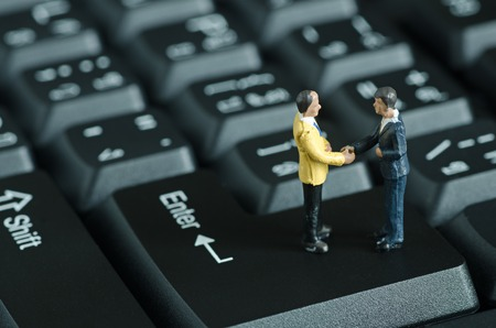 miniature people shake hand on keyboard backgroud
