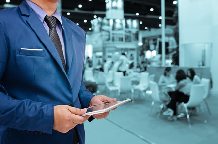 event: business man holding tablet with blurry event background