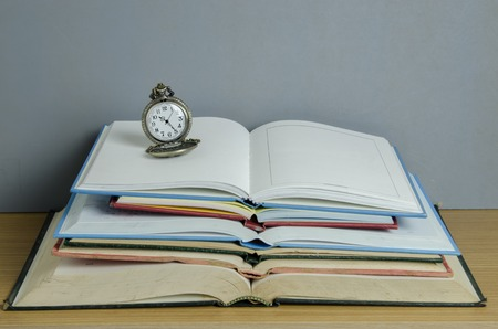 pendent: pendent clock on stack of open book