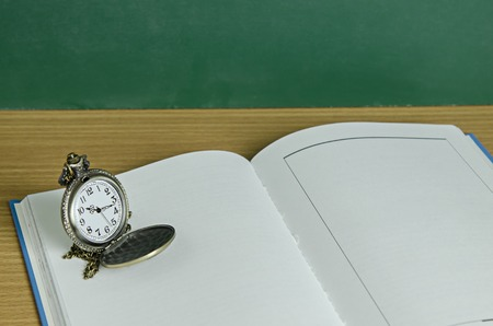 pendent: pendent clock on blank open book Stock Photo