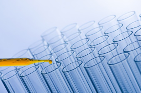 science laboratory pipette with drop on test tube background , laboratory concept