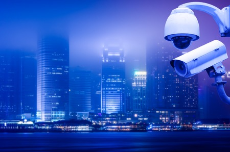 Surveillance Security Camera or CCTV over city Stock Photo