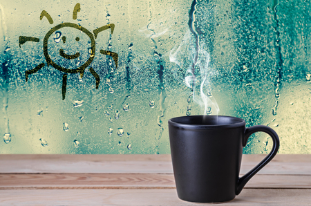 black coffee cup with smoke and sun sign on water drops glass window background Stockfoto