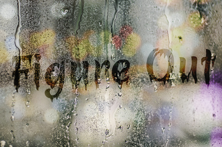 figure out: natural water drops on glass window with the text Figure Out