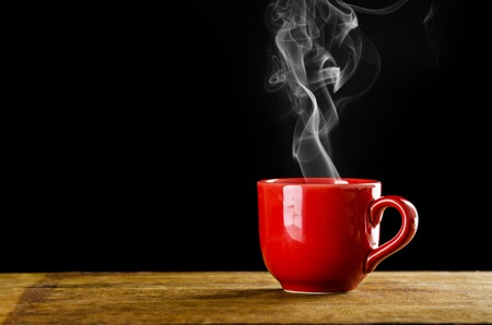 coffee mug: red coffee cup with smoke on black background Stock Photo