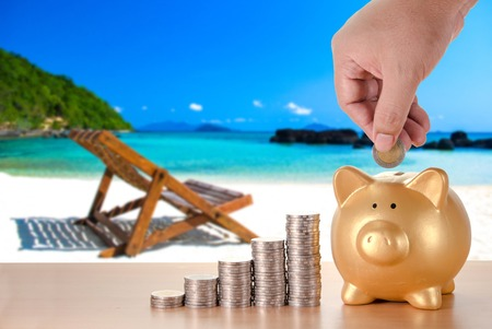 man hand with coins plan to saving money with gold piggy bank for beach vacation