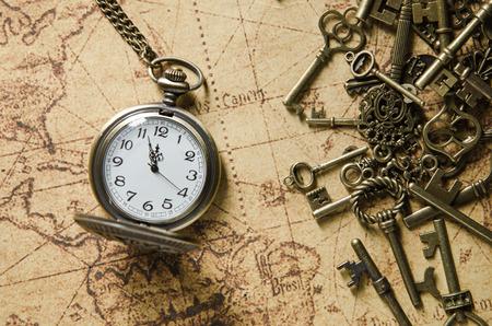 skeleton key: vintage pocket watch and skeleton key on ancient map background Stock Photo