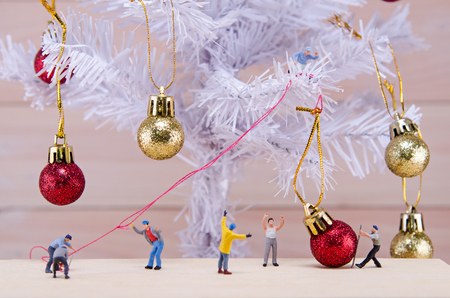 tree world tree service: miniature people try to ornament Christmas tree