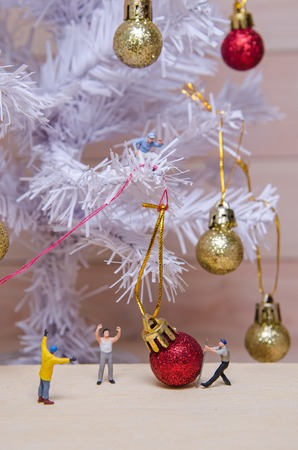 tree service business: miniature people try to ornament Christmas tree