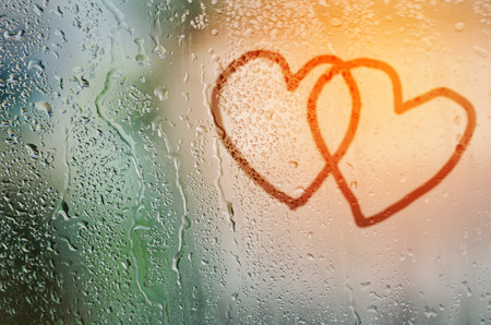 steamy: draw cople heart on natural water drops glass window background Stock Photo
