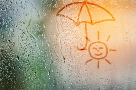 umbella: draw sun holding umbella on natural water drops glass window background